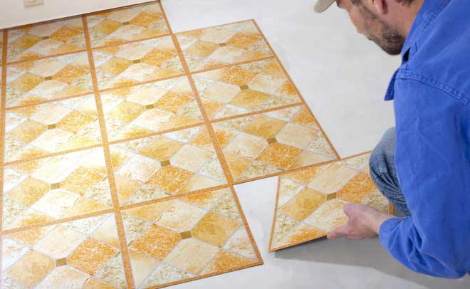 Man Installing Peel and Stick Vinyl Flooring Tiles