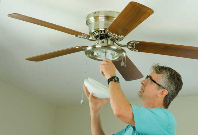 Man Performing Ceiling Fan Maintenance