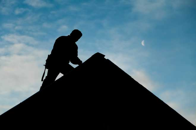 Silhouette of a Roofing Contractor on a Roof