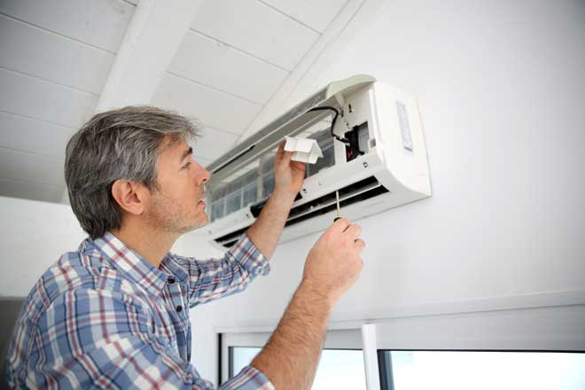 Repairman Fixing Mini Split Air Conditioner