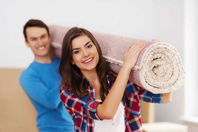 Couple Carrying Carpet Roll Into Home