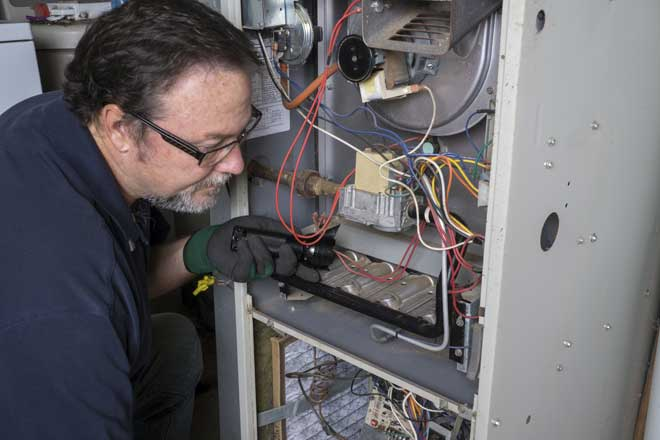HVAC Technician Looking at Gas Furnace