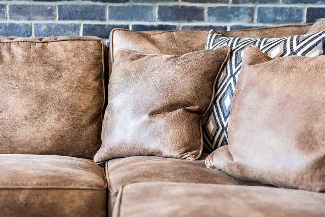 Leather Couch Next to Brick Wall