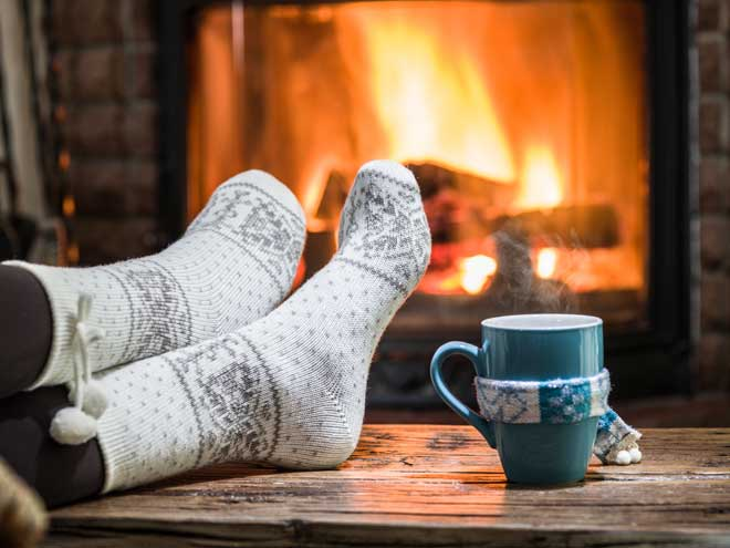 Person Relaxing by Fireplace with a Drink