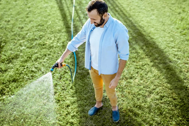 Man Watering Lawn with Garden Hose