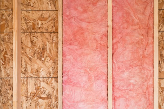 Fiberglass Insulation Being Installed in Wall